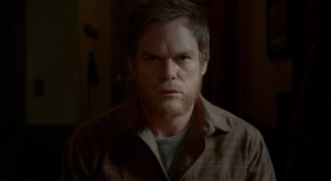 A bearded Dexter looks into the camera, as the series comes to an end